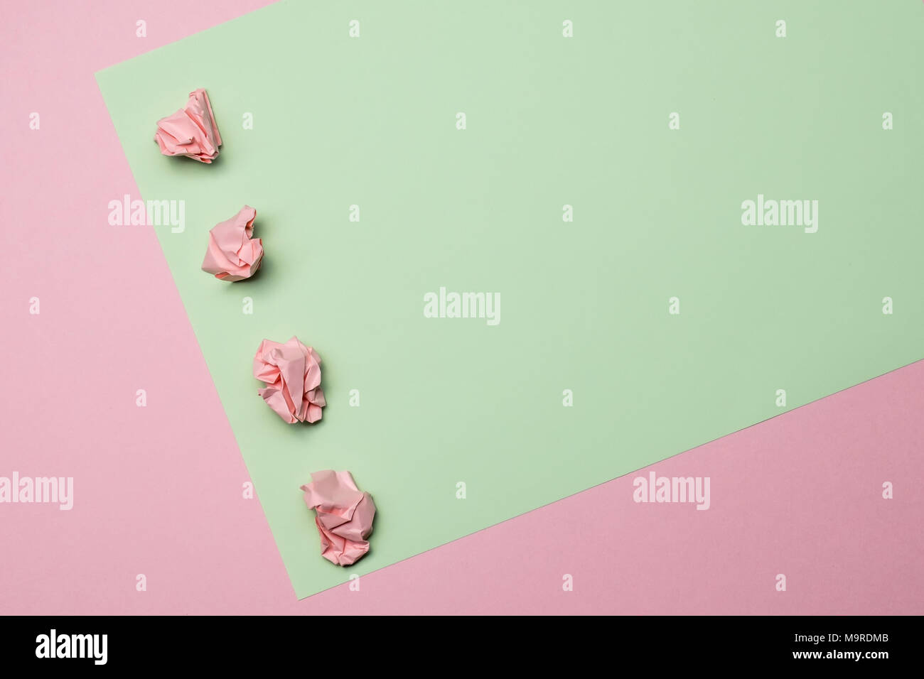Two tone pink and green contrast color paper background with crumpled balls. Empty blank for text, design and advertising. - Stock Image