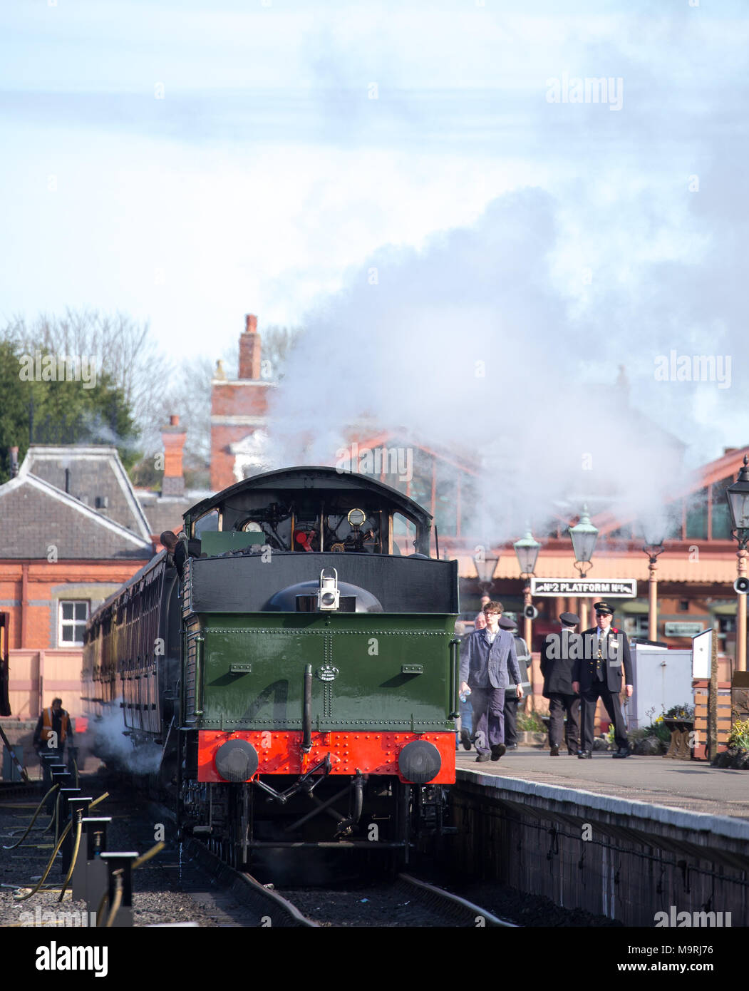 Portrait shot of UK steam locomotive in plumes of steam & smoke as crew prepare for bright Sunday morning departure from SVR's Kidderminster station. - Stock Image