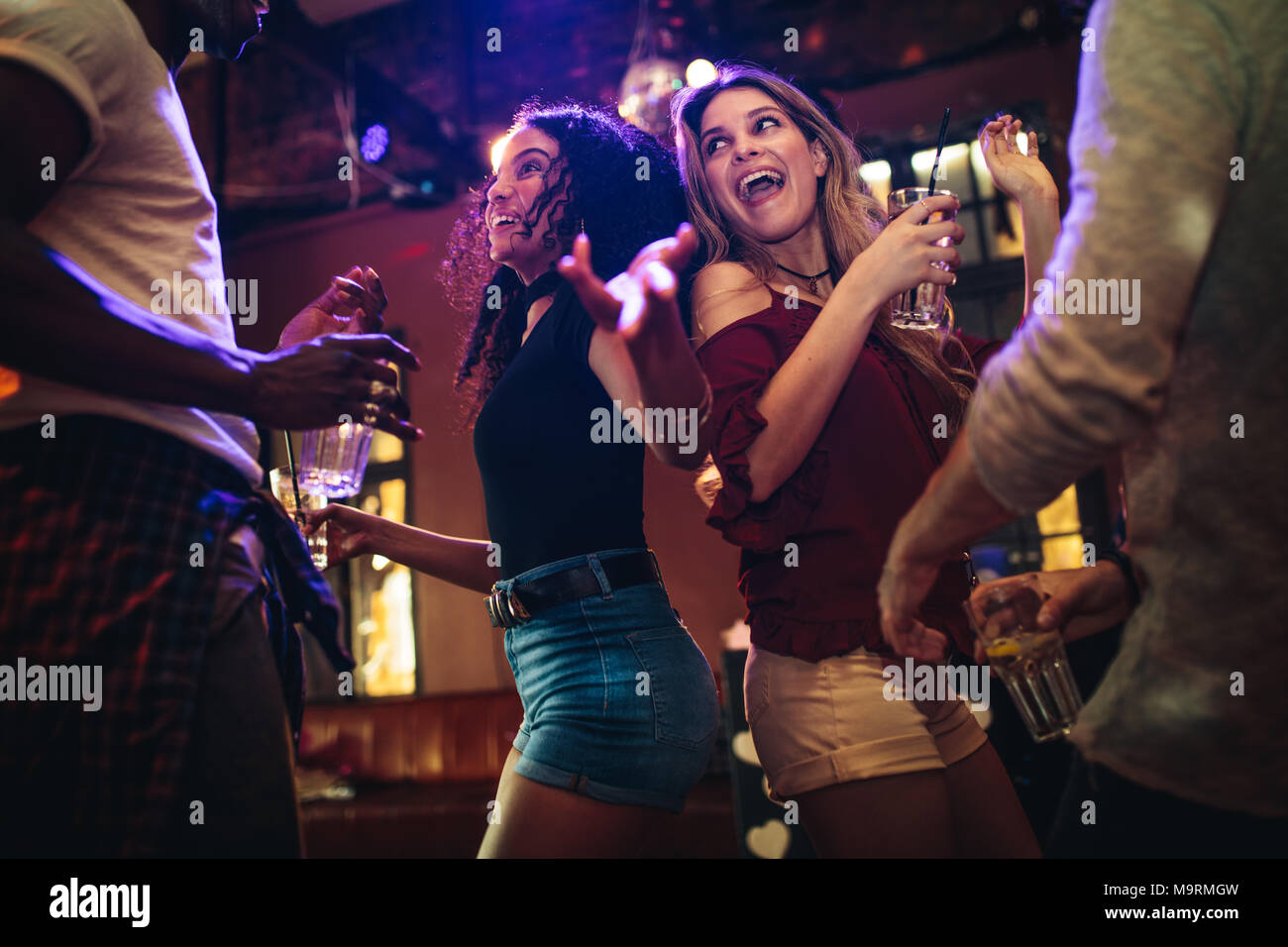 Happy young women dancing and partying with male friends at nightclub. Group of friends enjoying at bar with drinks. - Stock Image