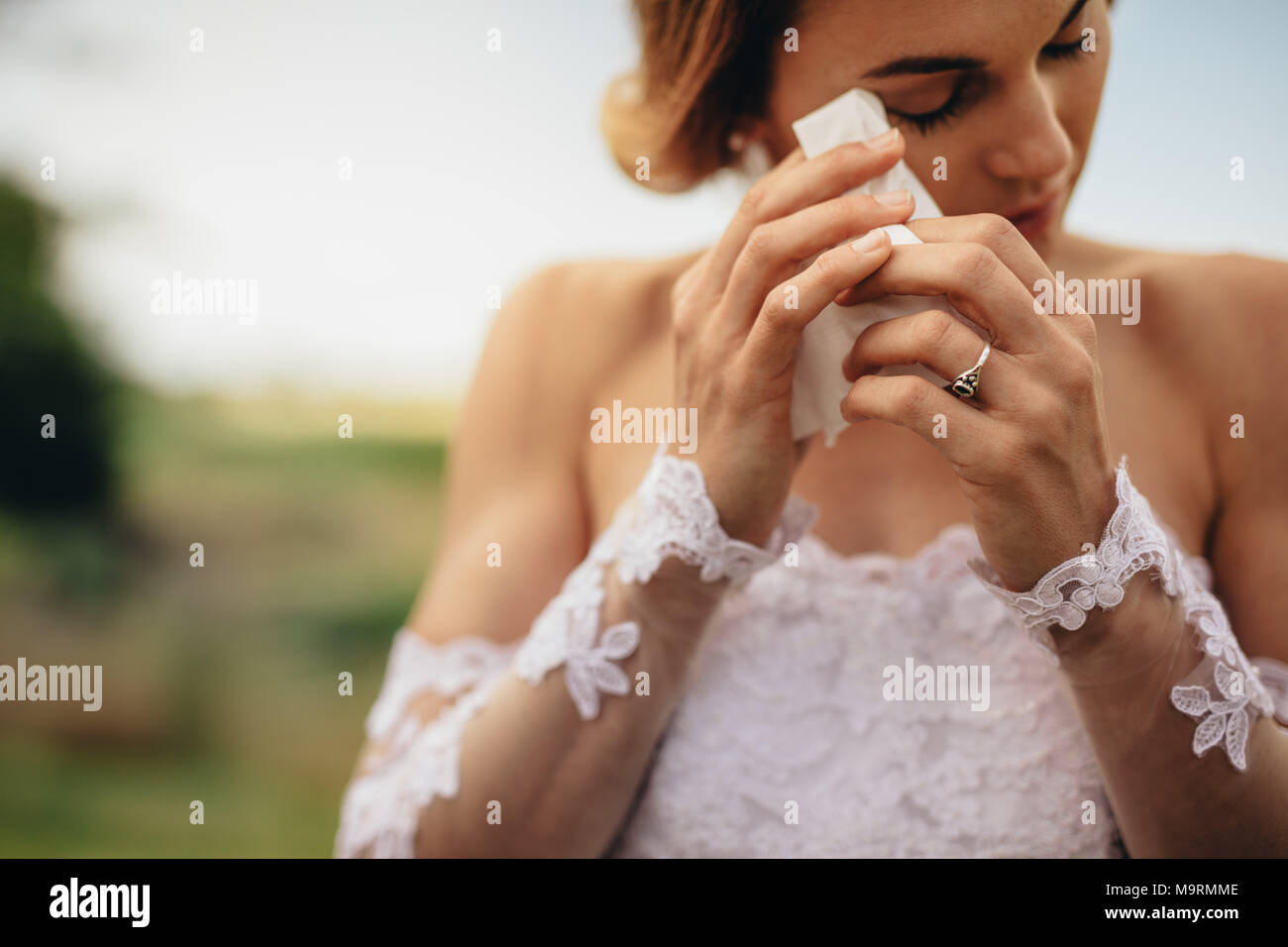 Beautiful bride in white dress weeps tears of happiness on the wedding day. Emotional woman in wedding gown wipes the tears with tissue paper. - Stock Image