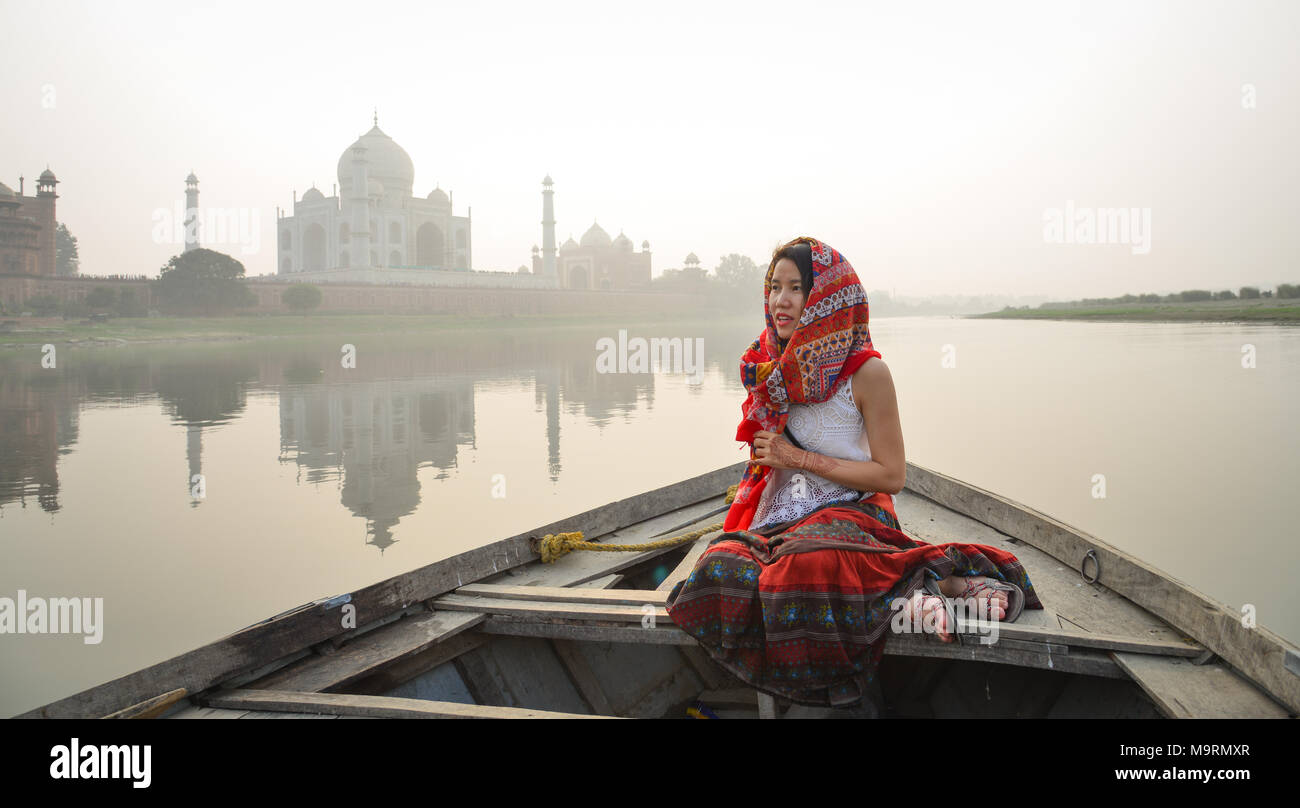 A woman watching sunset over Taj Mahal from a wooden boat. Stock Photo