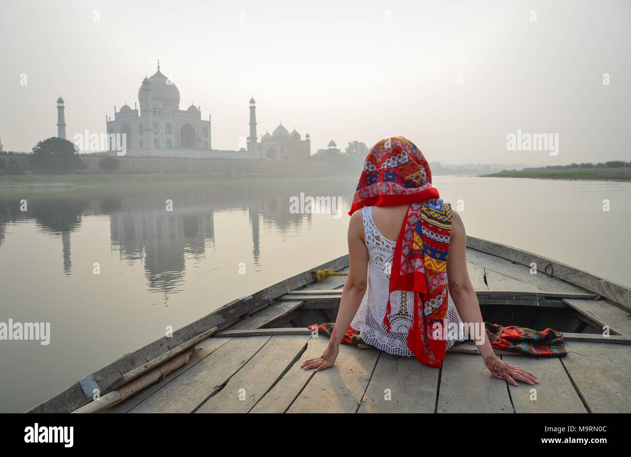 An Asian woman watching sunset over Taj Mahal from a wooden boat. Stock Photo