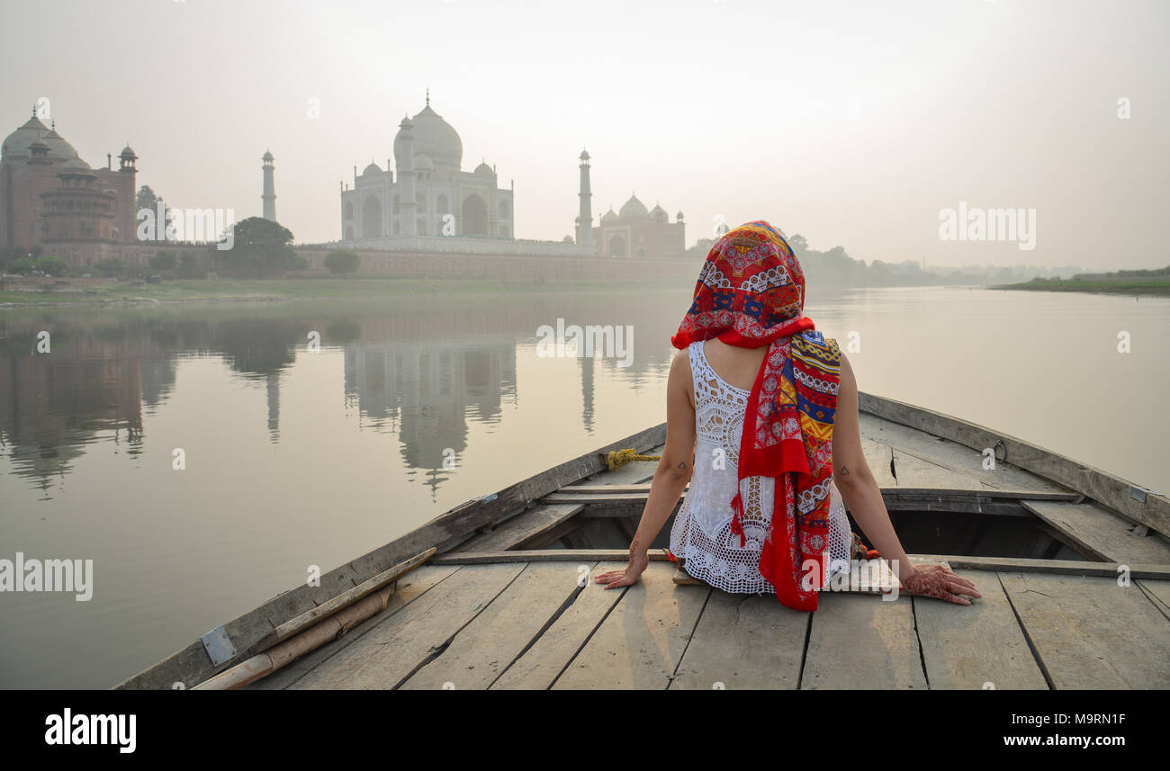 A young woman watching sunset over Taj Mahal from a wooden boat. Stock Photo