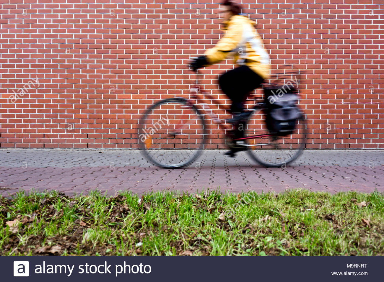 motion blur of a woman in yellow jacket riding on a bicycle in the city streets - Stock Image