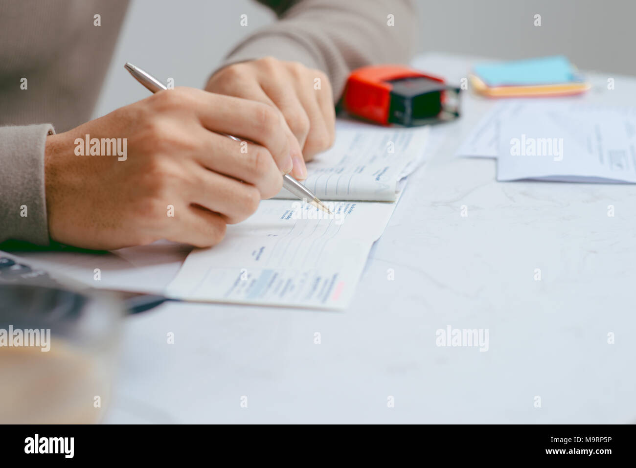 Man writing a payment check at the table with calculator and stamp - Stock Image