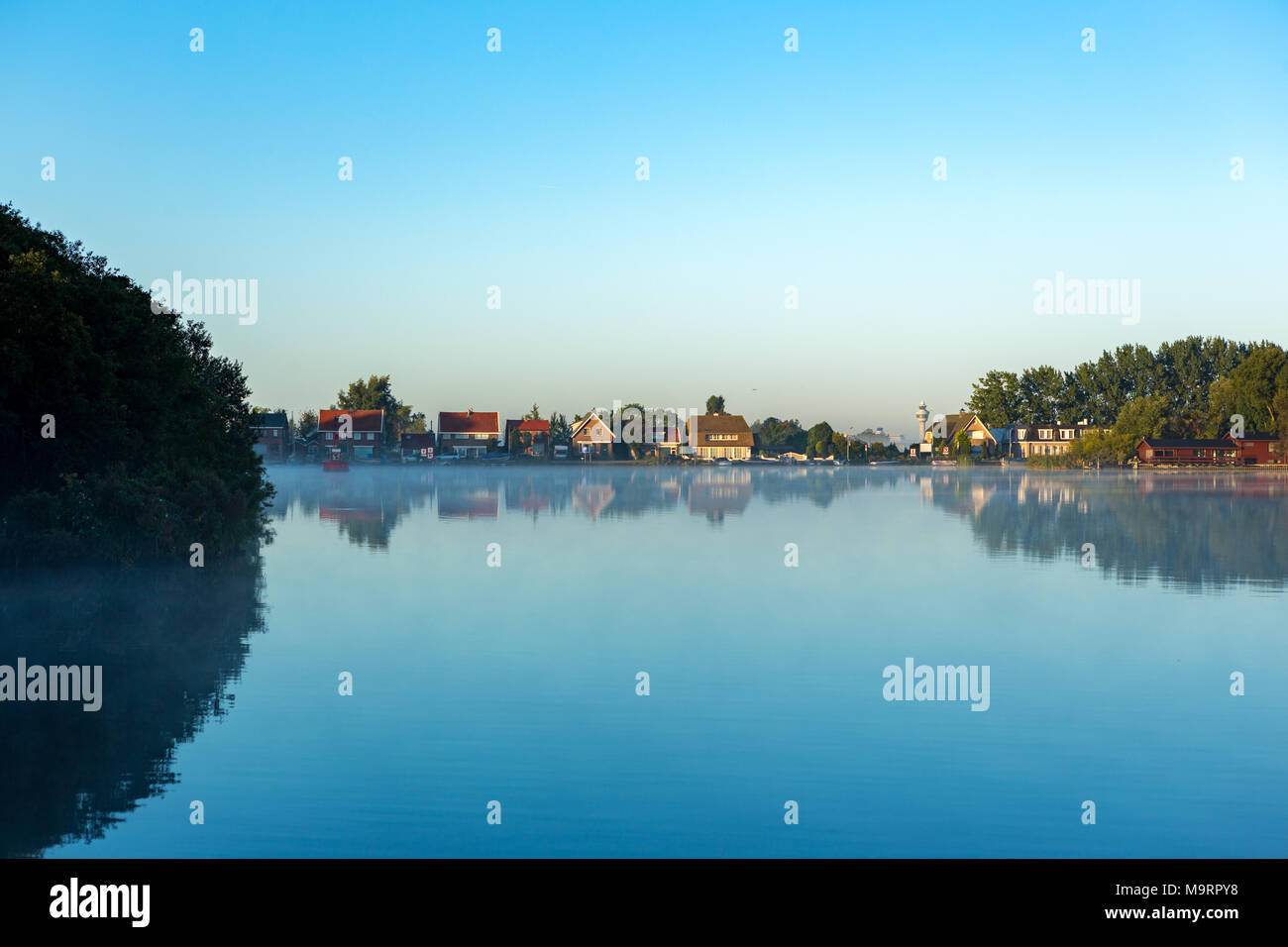 Airtrafic tower and houses on a windless and foggy morning at lake 'Nieuwe Meer' in Amsterdam the Netherlands. - Stock Image