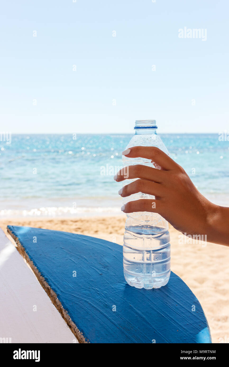 Female hand holding a bottle of water on the beach, sea background. - Stock Image