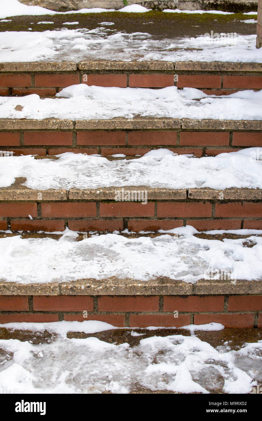 Compacted snow that has frozen on steps during freezing weather UK - Stock Image