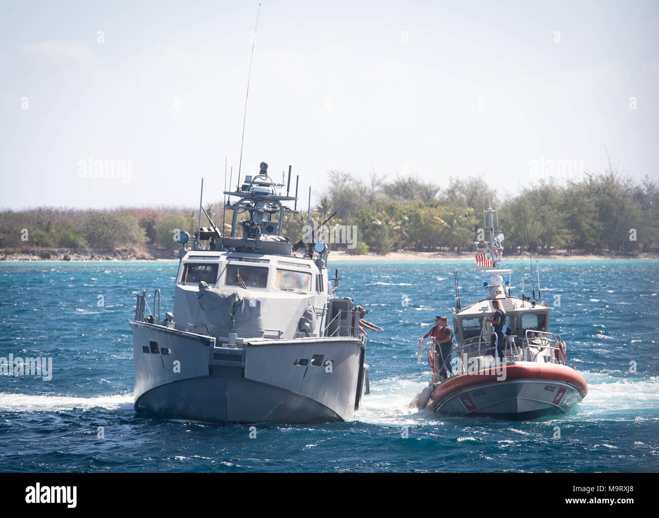 Sailors assigned to Coastal Riverine Squadron (CRS) 4, Det. Guam reach for a line from U.S. Coast Guard Sailors aboard a 47-foot Motor Lifeboat, assigned to U.S. Coast Guard Sector Guam, during a towing exercise in Apra Harbor, Guam, March 28, 2018. CRS-4, Det. Guam is assigned to Commander, Task Force 75, the primary expeditionary task force responsible for planning and execution of coastal riverine operations, explosive ordnance disposal, diving engineering and construction, and underwater construction in the U.S. 7th Fleet area of operations. (U.S. Navy Combat Camera photo by Mass Communica Stock Photo