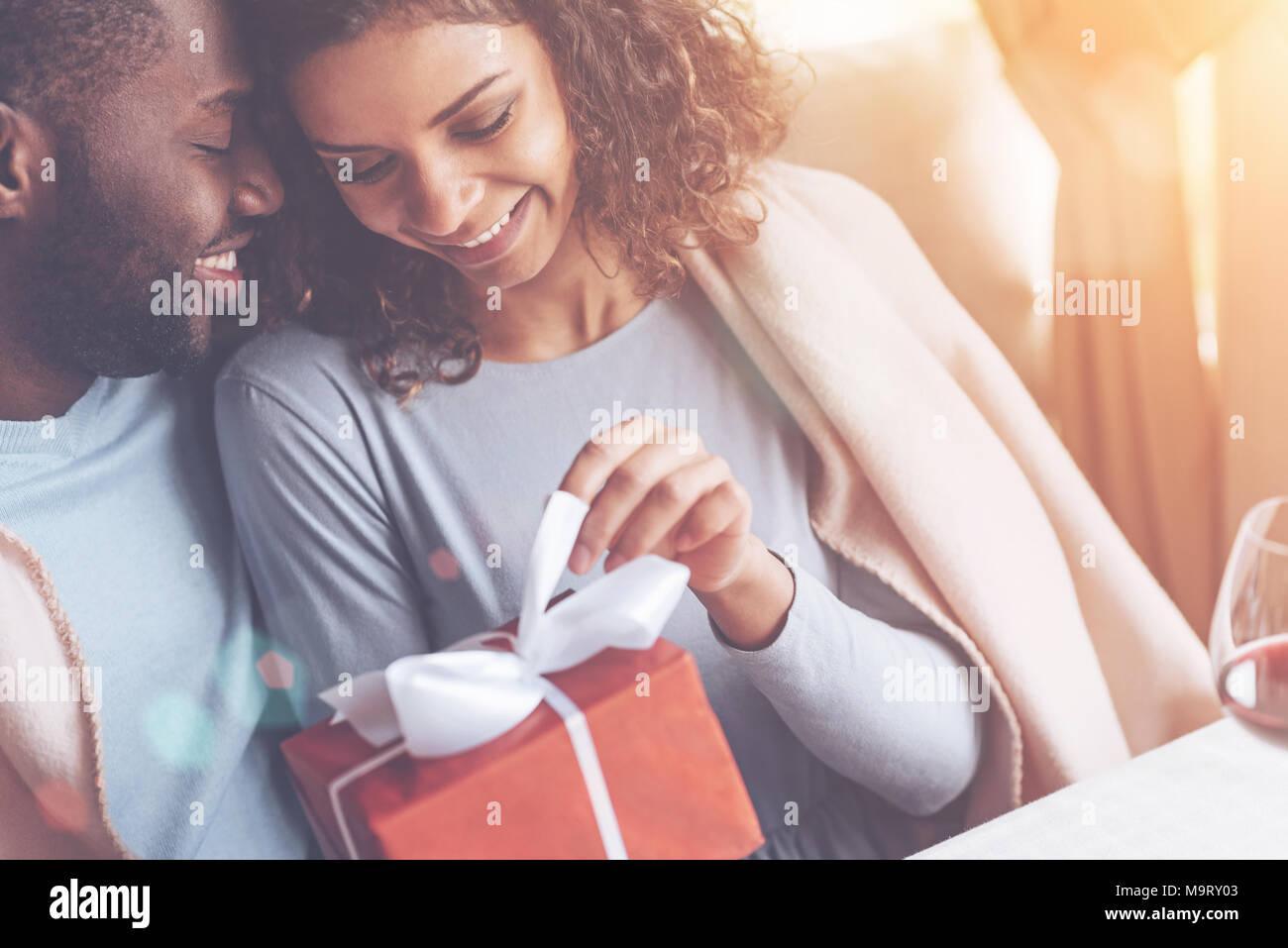 Delighted dark-skinned female touching white ribbon - Stock Image