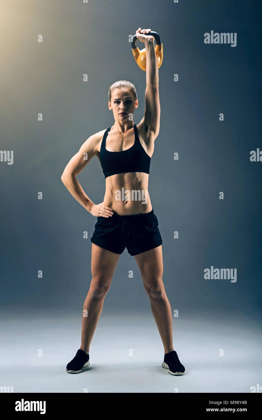 Strong female athlete swinging kettlebell while exercising - Stock Image