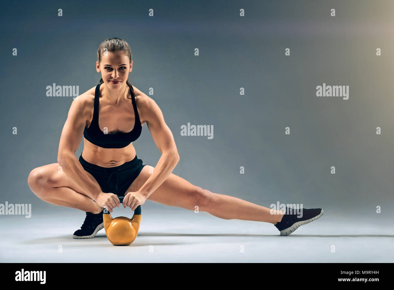 Friendly looking muscular girl posing with kettlebell - Stock Image