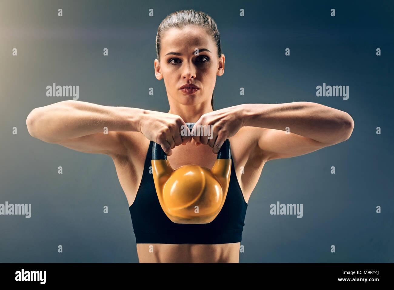 Strong muscular sportswoman holding heavy kettlebell - Stock Image