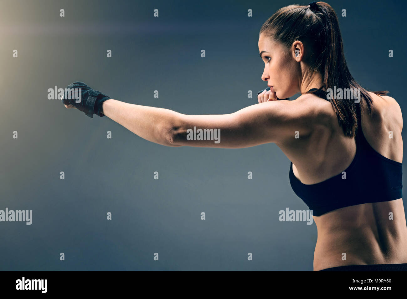 Side view of young sportswoman punching over background - Stock Image