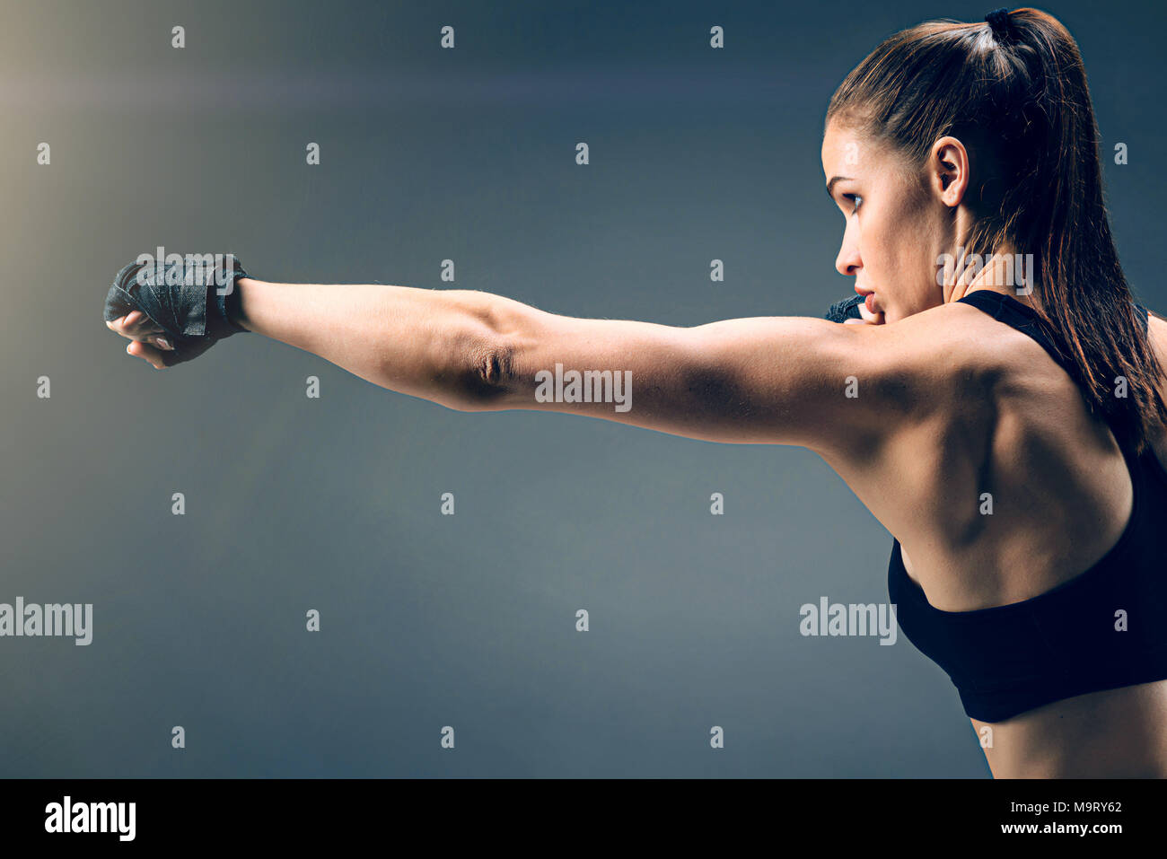Focused fit brunette boxing confidently - Stock Image