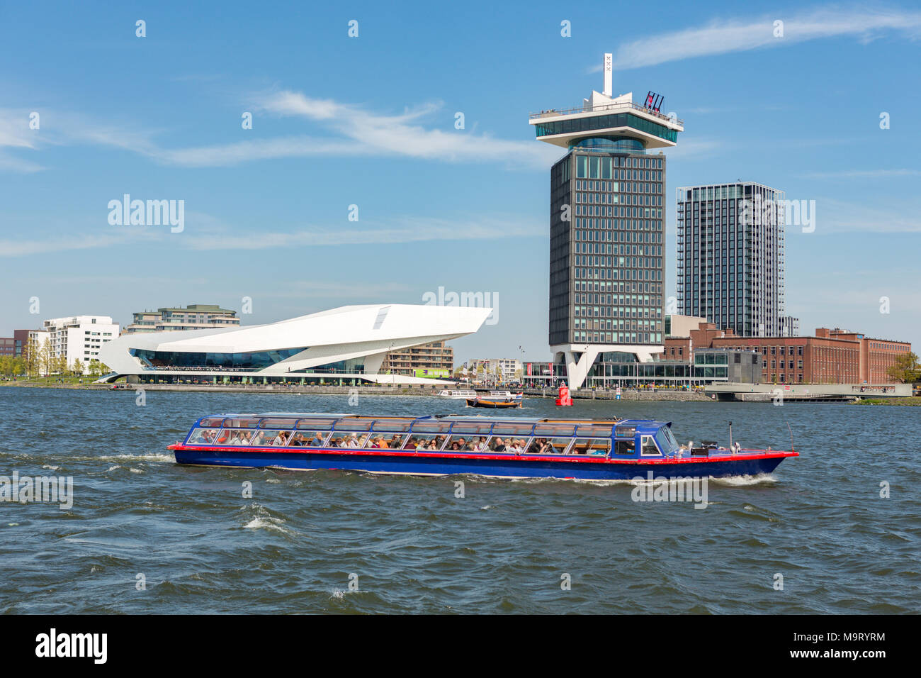 EYE Filmuseum and the A'DAM Lookout tower over 't IJ river on a sunny day in Amsterdam Noord in The Netherlands. - Stock Image