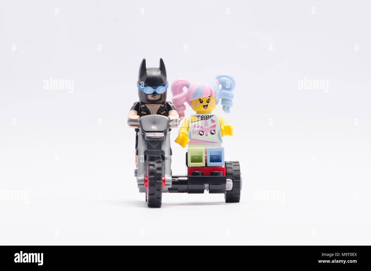 lego batman riding dirt bike with n-pop girl . isolated on white background. - Stock Image