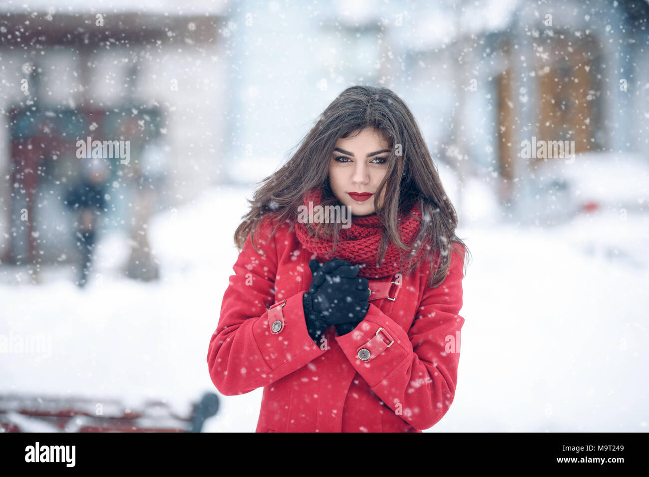 db33784eeb536 Winter portrait of young beautiful brunette woman wearing knitted snood and  red coat covered in snow. Snowing winter beauty fashion concept. snowing