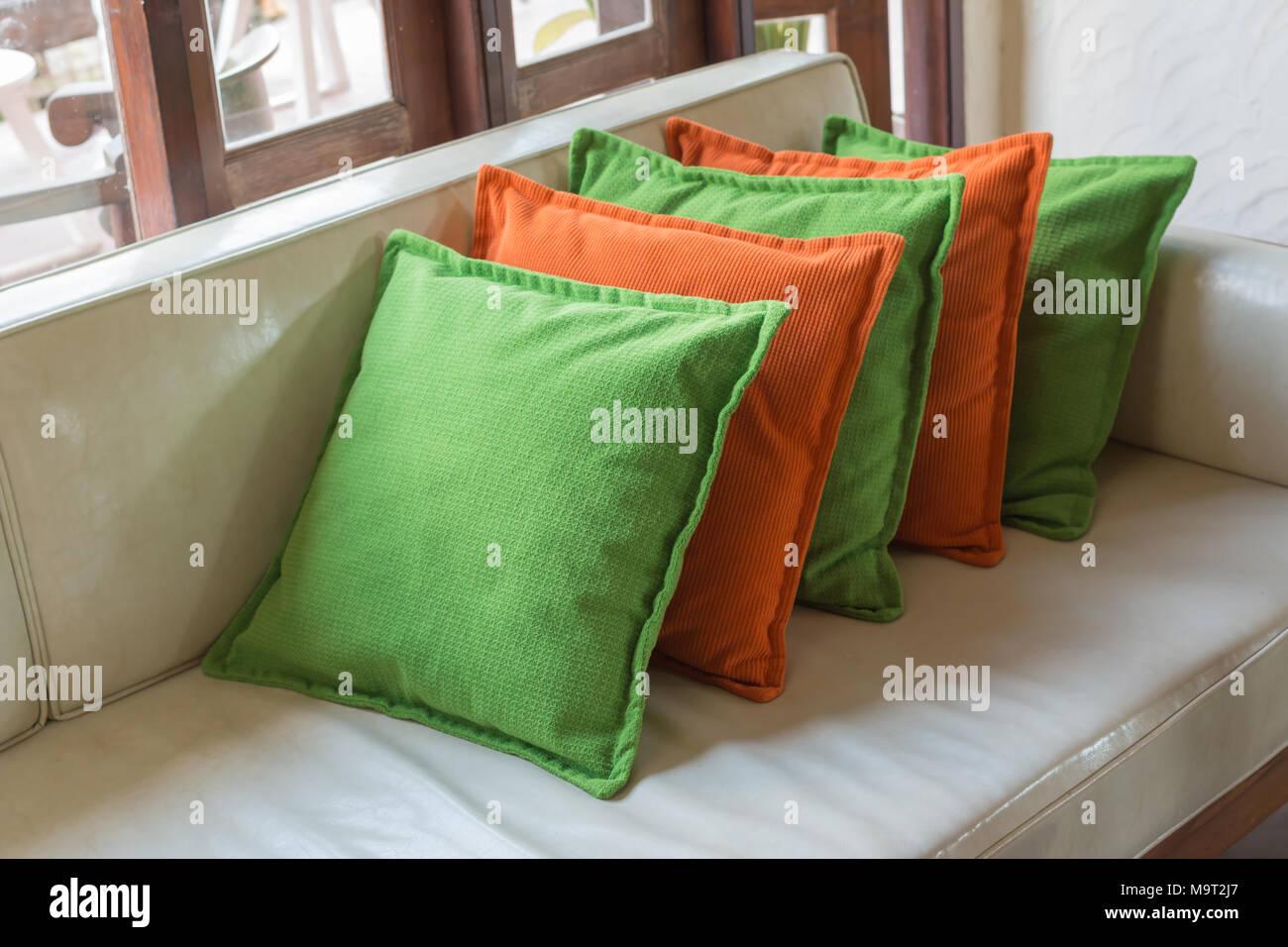 Orange and green Decorative pillows on white leather sofa ...