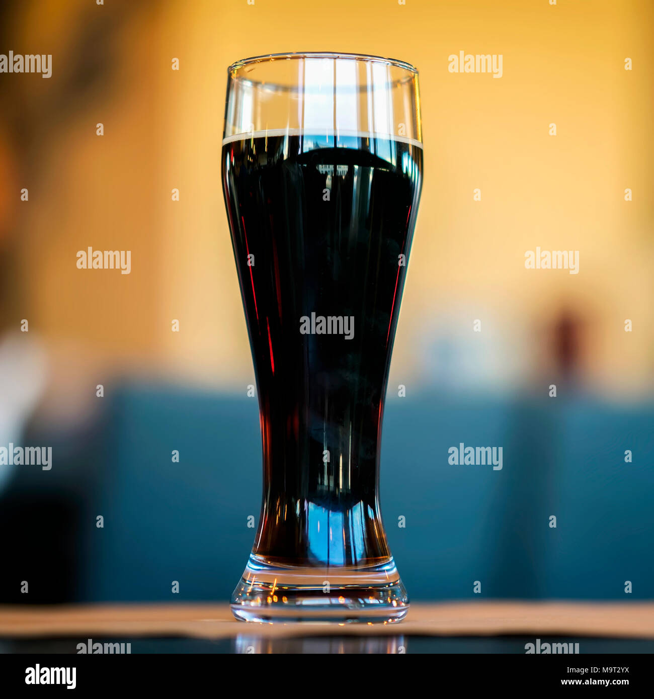 Glass of dark beer in bar or in pub close up. Real scene. Concept of beer culture, Craft brewery, festivals and meetings low-alcohol beverage lovers - Stock Image
