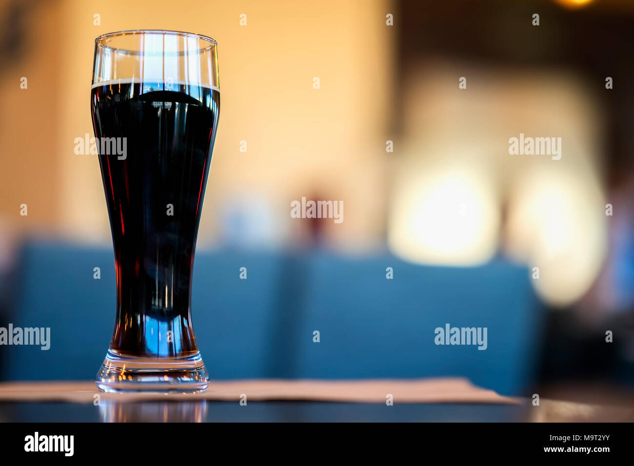 Glass of dark beer in bar or in pub close up. Real scene. Concept of beer culture, Craft brewery, uniqueness of beer grades, meeting of low alcohol beverage lovers - Stock Image
