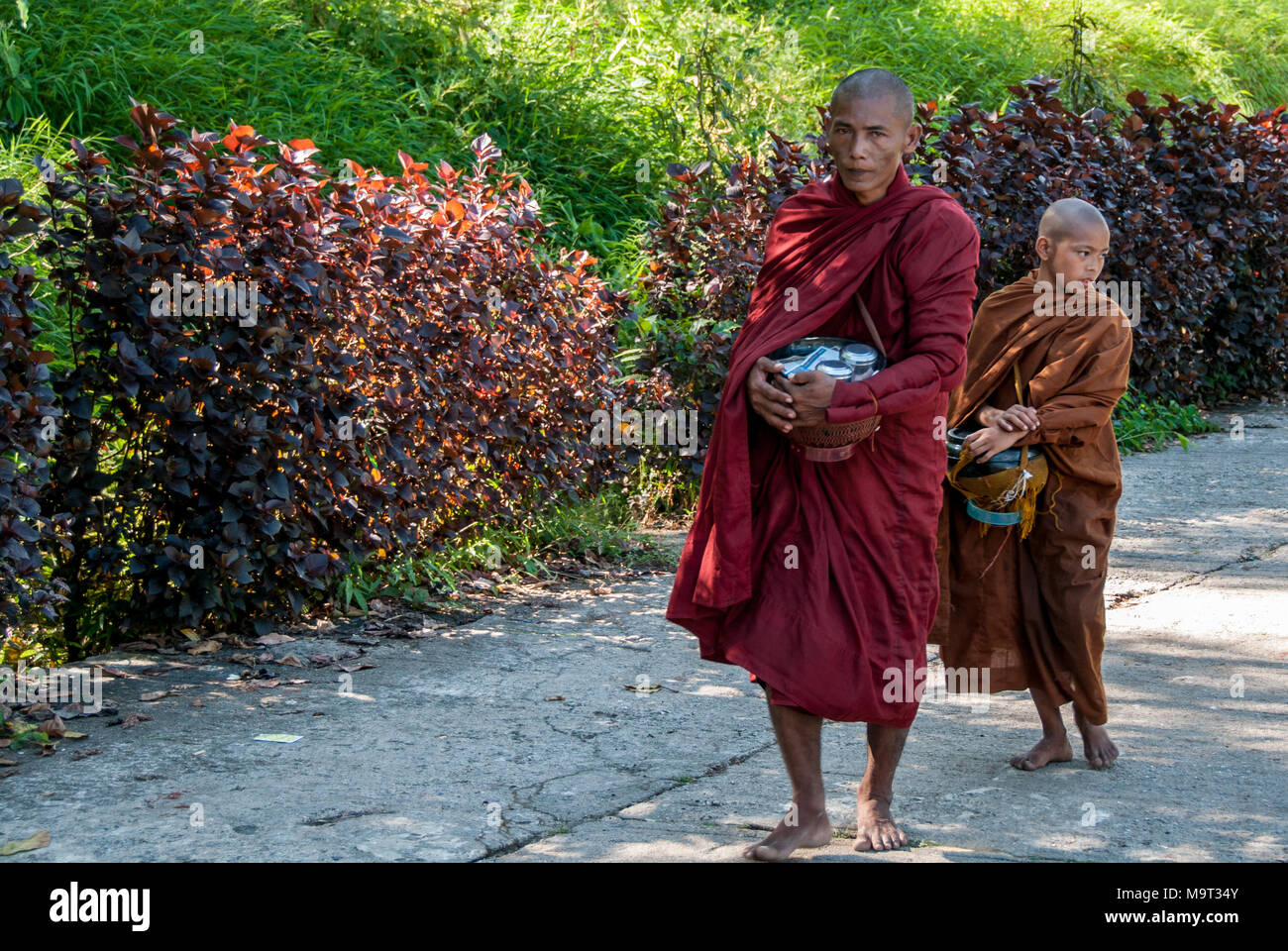 a monk ascends to the Golden Rock Pagoda followed by his disciple - Stock Image