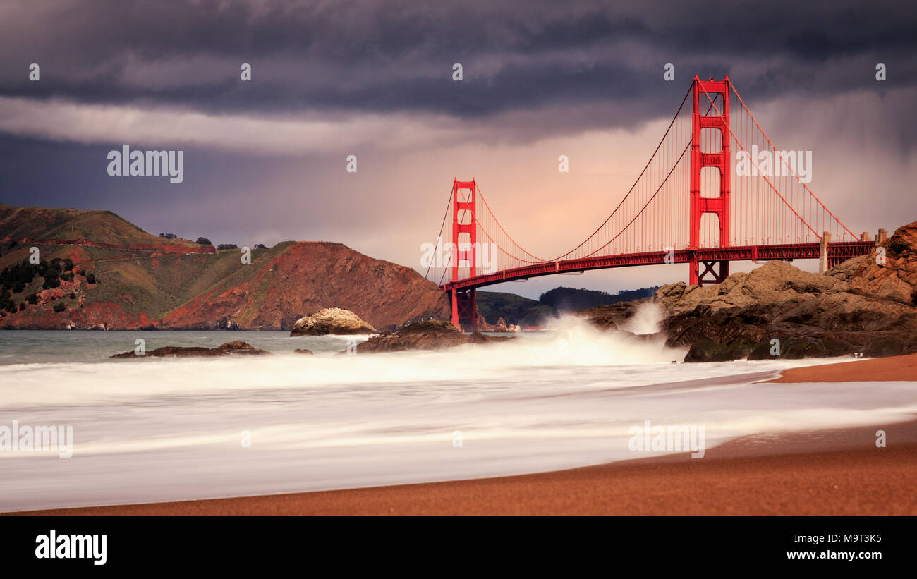 Dramatic mid-afternoon stormy sky over Golden Gate Bridge with crashing waves on Baker Beach - Stock Image