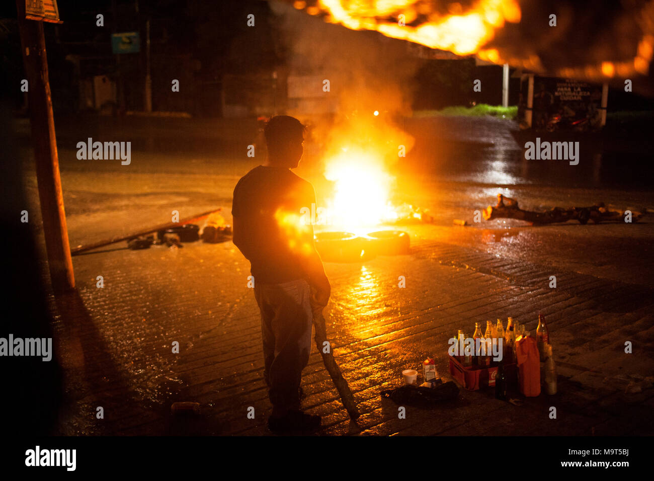 A man watches a fire outside a barricade blocking access to a barrio in Tixtla, Guerrero, Mexico on June 7, 2015.   The barricade was set up the day before midterm elections to prevent police or rival political militia groups entering the barrio. - Stock Image