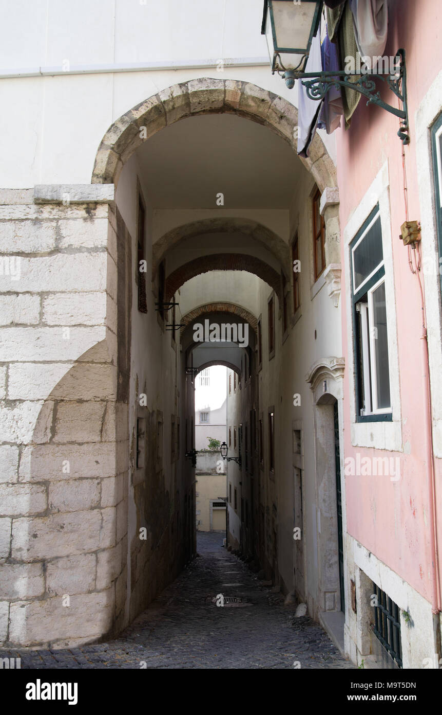 Narrow And Sloped Cobblestone Street Under A Tall Archway In Alfama  Disctrict, The Most Famous