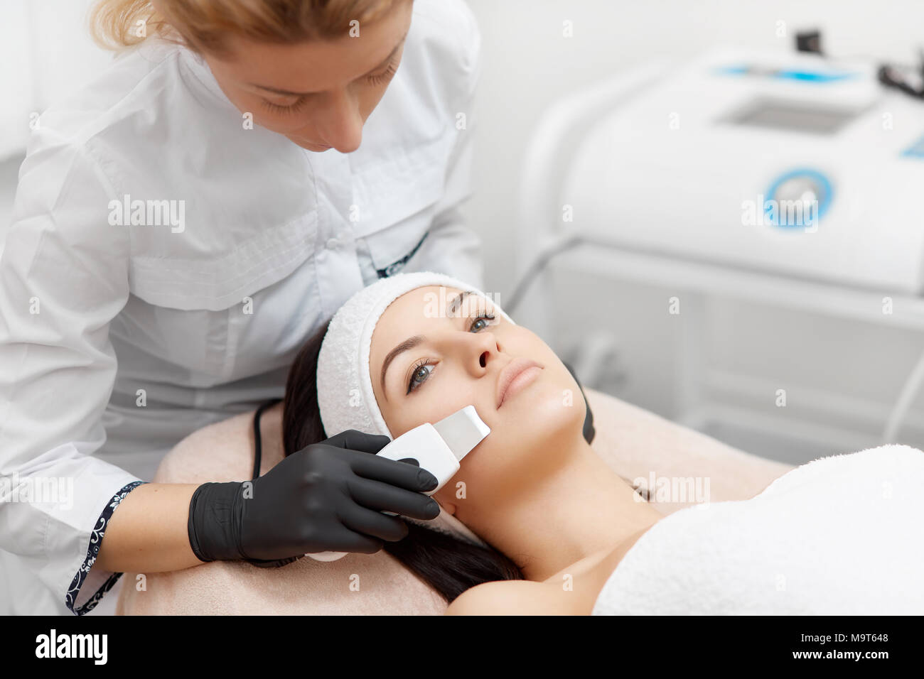 Beauty salon procedures of ultrasonic cleaning of face. - Stock Image