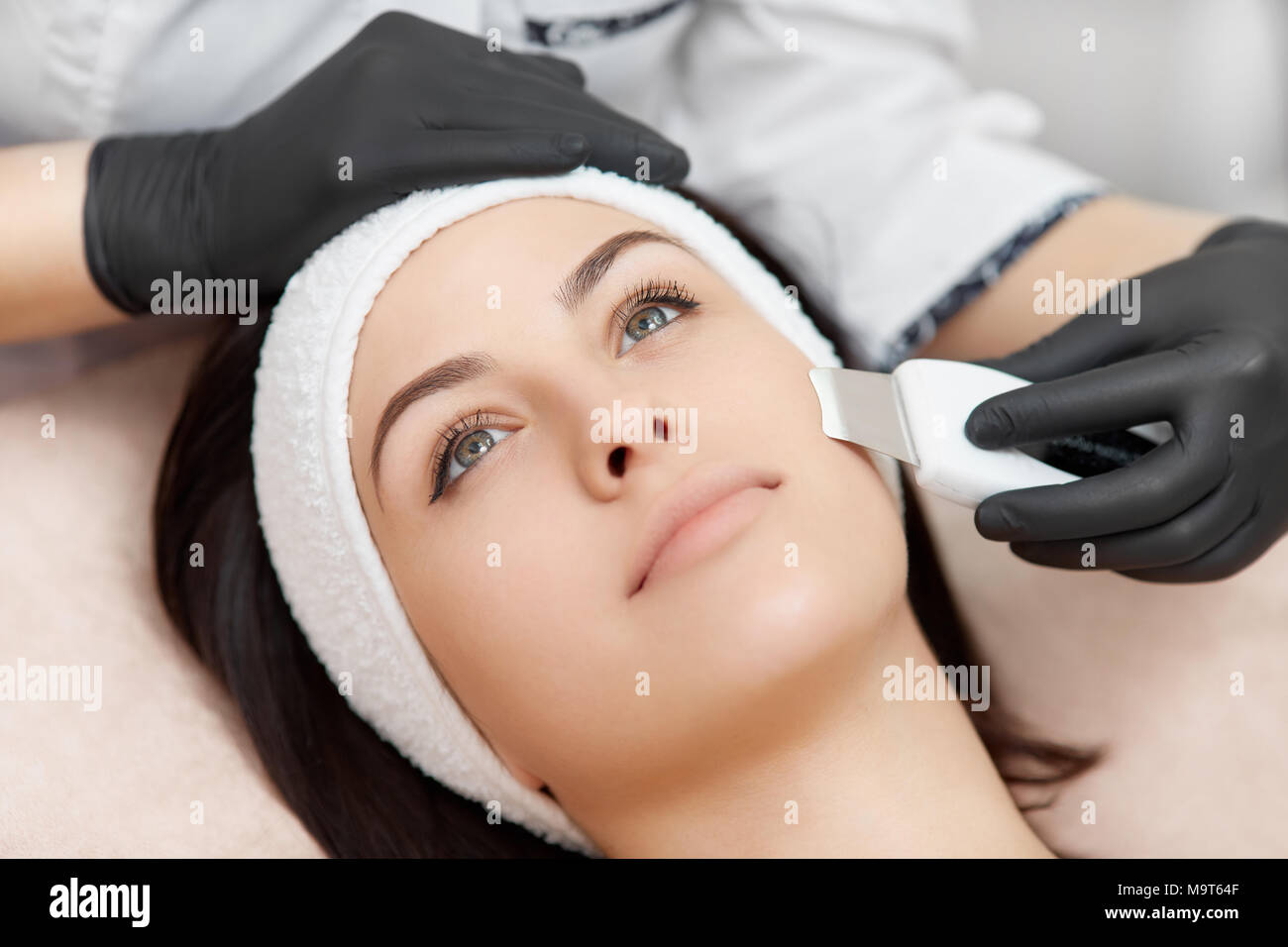 Facial ultrasonic cleaning with special device in beauty salon. - Stock Image