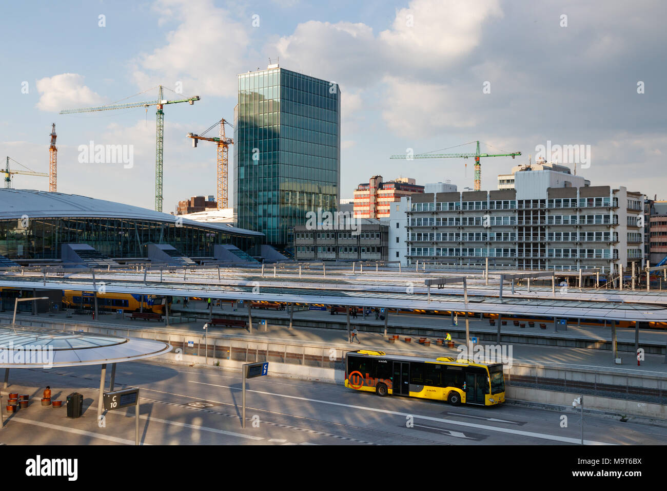The NS hea quarters, platforms of Utrecht Centraal Railway Station and the bus station with a leaving bus on a sunny day.  Utrecht, The Netherlands. - Stock Image