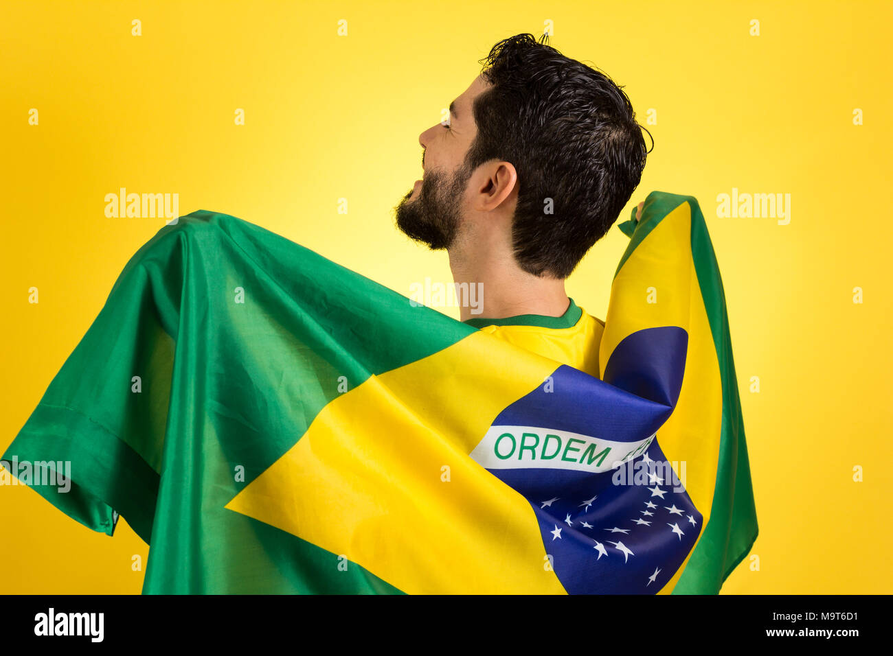 190a40e8d Brazilian soccer football team player. One supporter and fan holding Brazil  flag. Wearing yellow uniform on yellow backdrop.