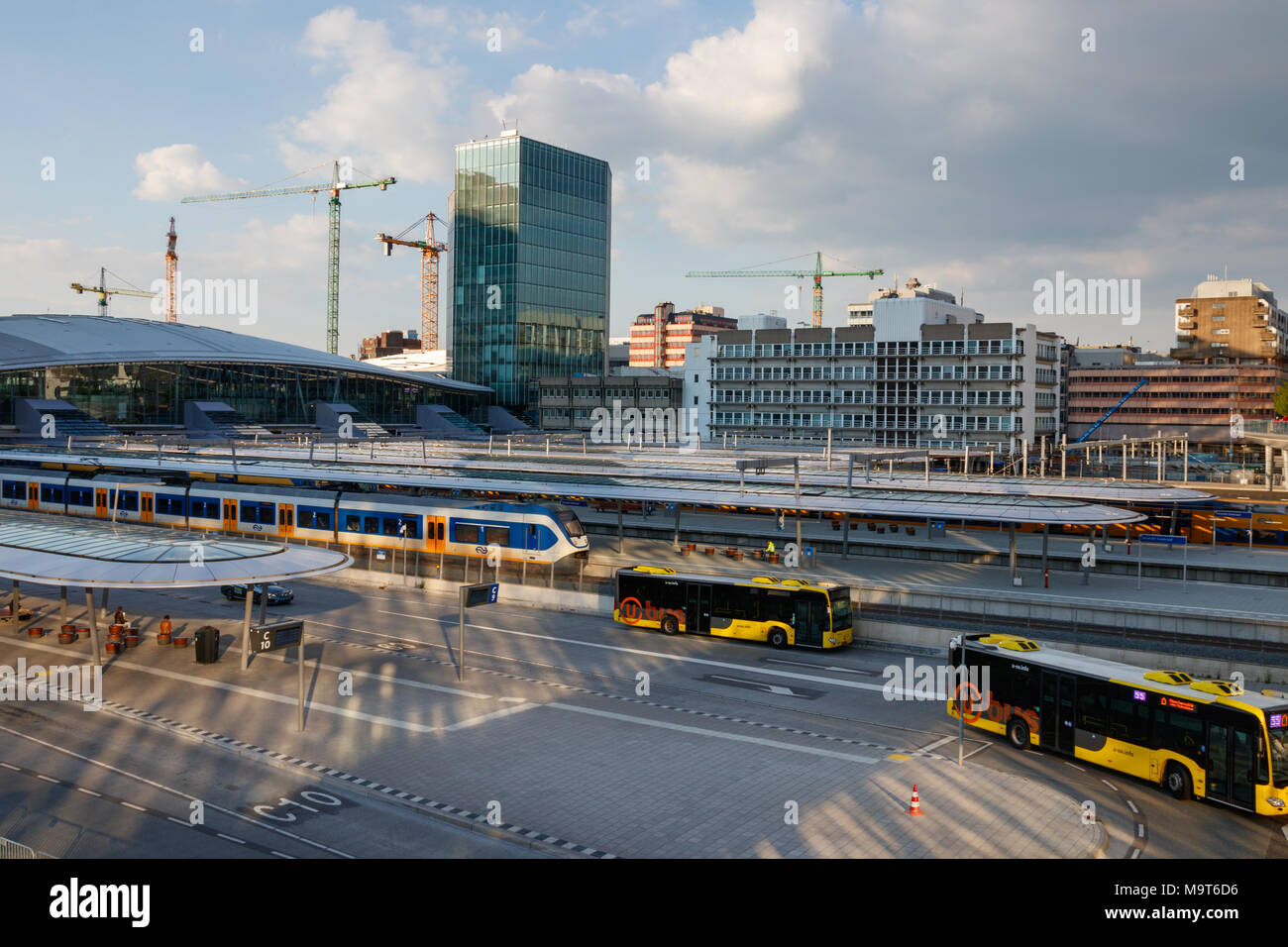 Platforms of Utrecht Centraal Railway Station with trains and the bus station with leaving buses on a sunny day. Utrecht, The Netherlands. - Stock Image