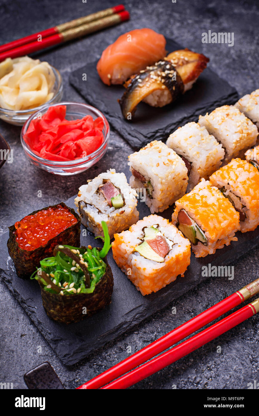 Sushi and roll set on black table - Stock Image