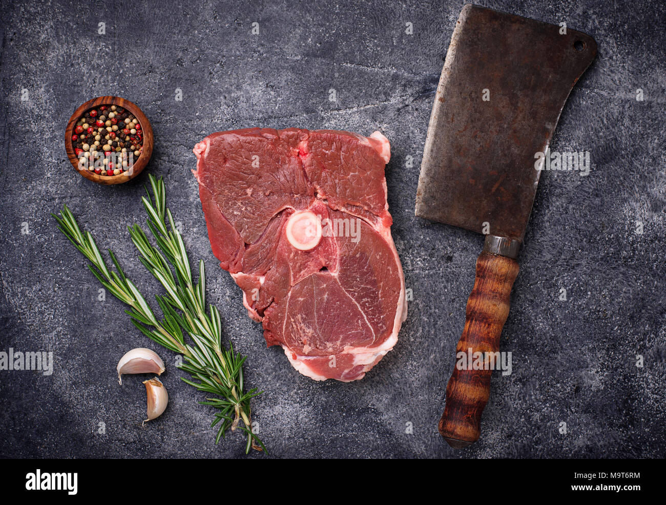 Lamb meat with rosemary, spices and cleaver.  - Stock Image