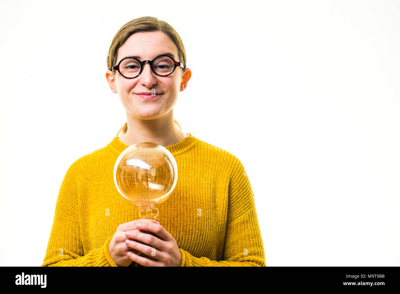Inspiration and Creativity - the lightbulb moment: A young 'geeky' looking Caucasian woman girl wearing a yellow jumper sweater  and round glasses, holding an old retro-style elecric light bulb  , against a white background, UK - Stock Image