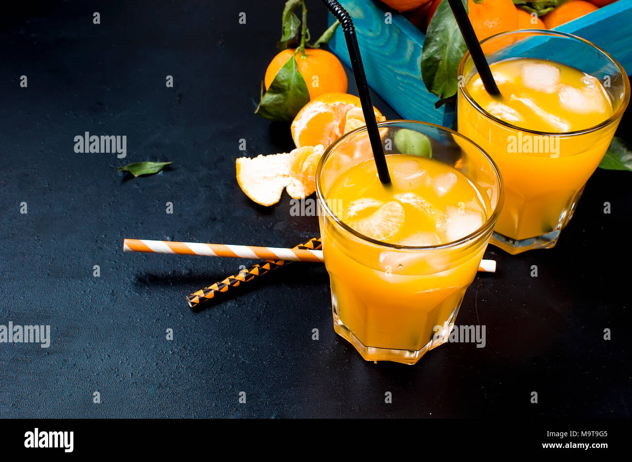 refreshing cocktail with tangerines, juice and ice in two glasses on a black background, alcoholic drink, copy space - Stock Image