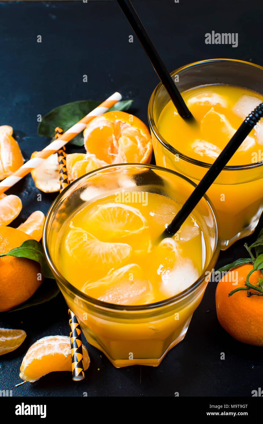 refreshing cocktail with tangerines, juice and ice in two glasses on a black background, alcoholic drink, copy space Stock Photo