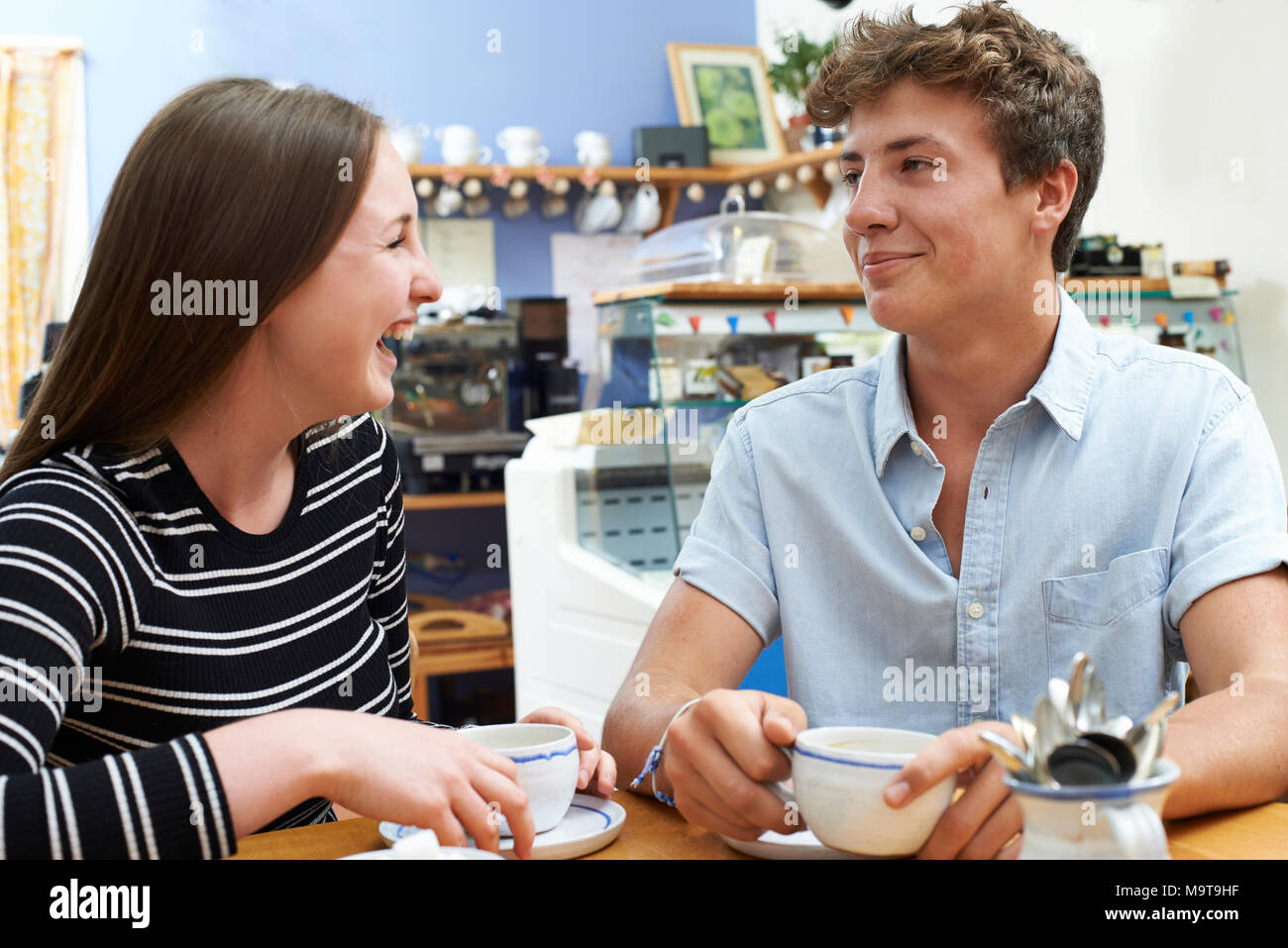 Teenage Couple Meeting In Cafe And Drinking Cup Of Coffee - Stock Image