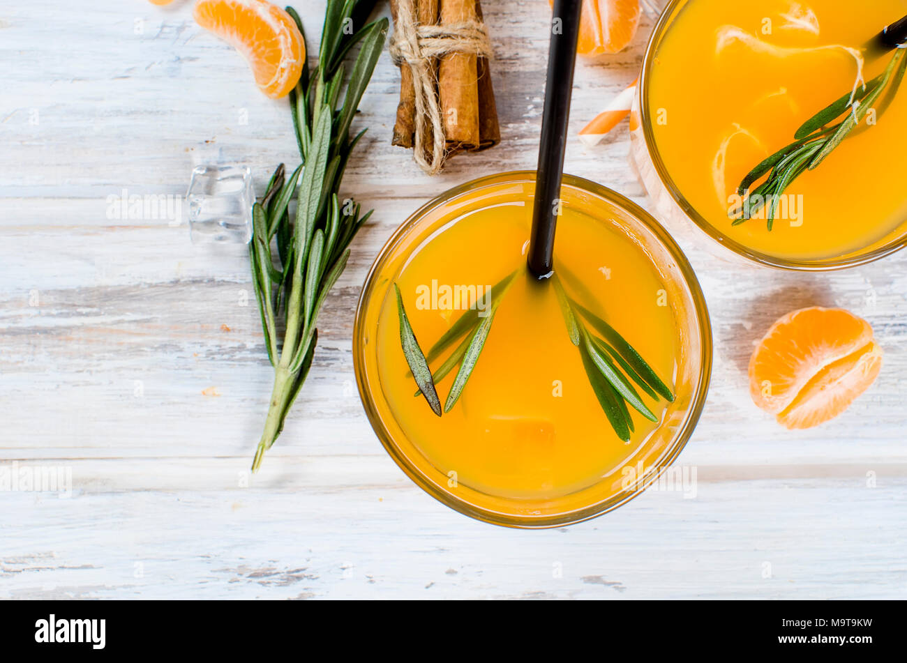 refreshing cocktail with tangerines, juice and ice in two glasses on a white wooden background, alcoholic drink, copy space Stock Photo