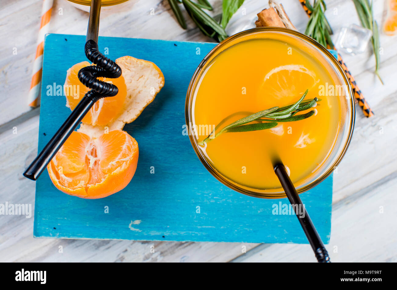 refreshing cocktail with tangerines, juice and ice in glass on a white wooden background, alcoholic drink, copy space - Stock Image