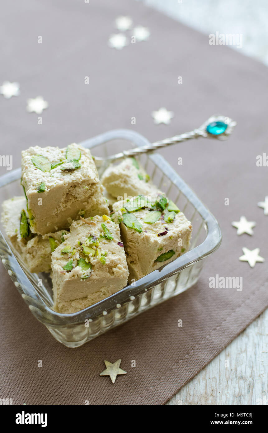 Halva pistachio - traditional eastern desserts. Arabian sweets on wooden table. Turkish delight concept. - Stock Image