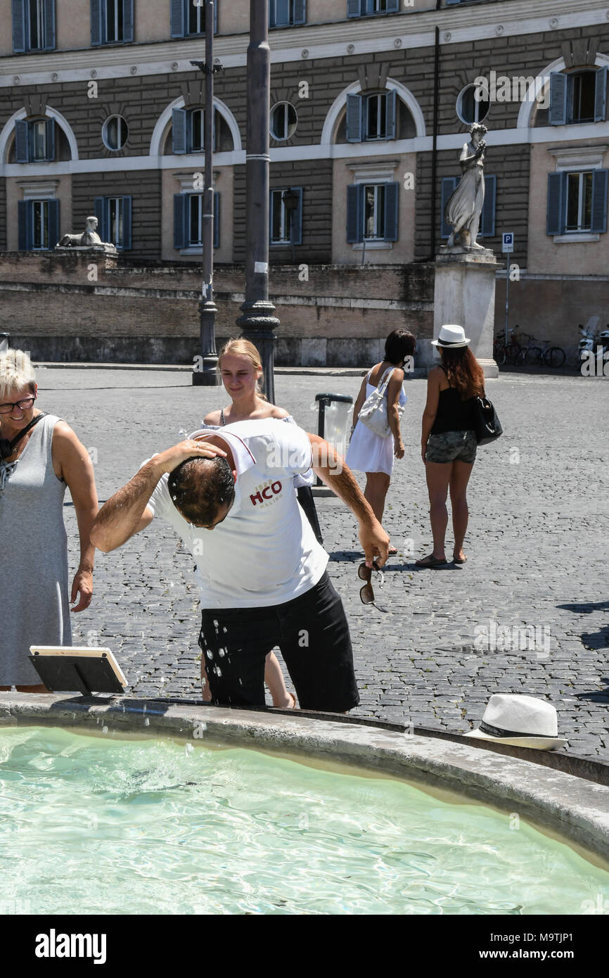 People cooling of in one of Rome's many fountains on a scorching hot day in the Italian capital in July 2017 - Stock Image