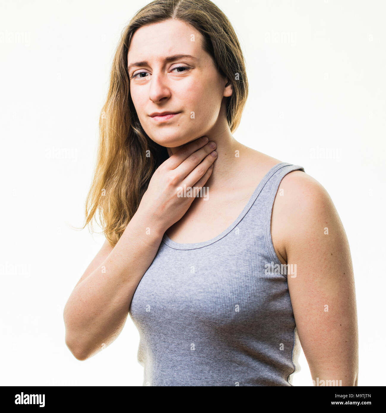 A young Caucasian woman girl wearing a grey vest,  suffering from a sore throat or neck pain, rubbing her skin for relief,  standing against a white background, UK - Stock Image