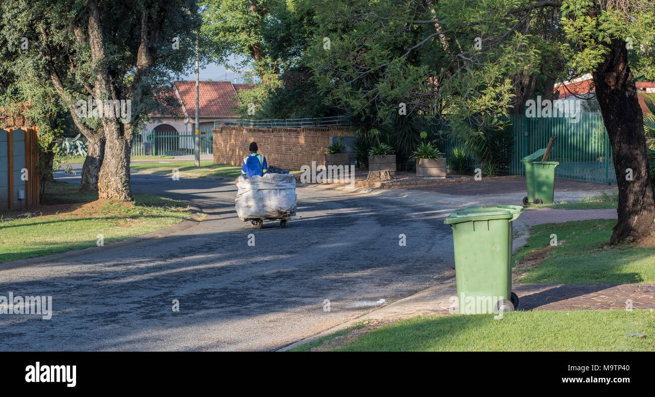 Johannesburg, South Africa - unidentified jobless man uses a makeshift trolley to collect recyclable products for resale from household refuse bins - Stock Image