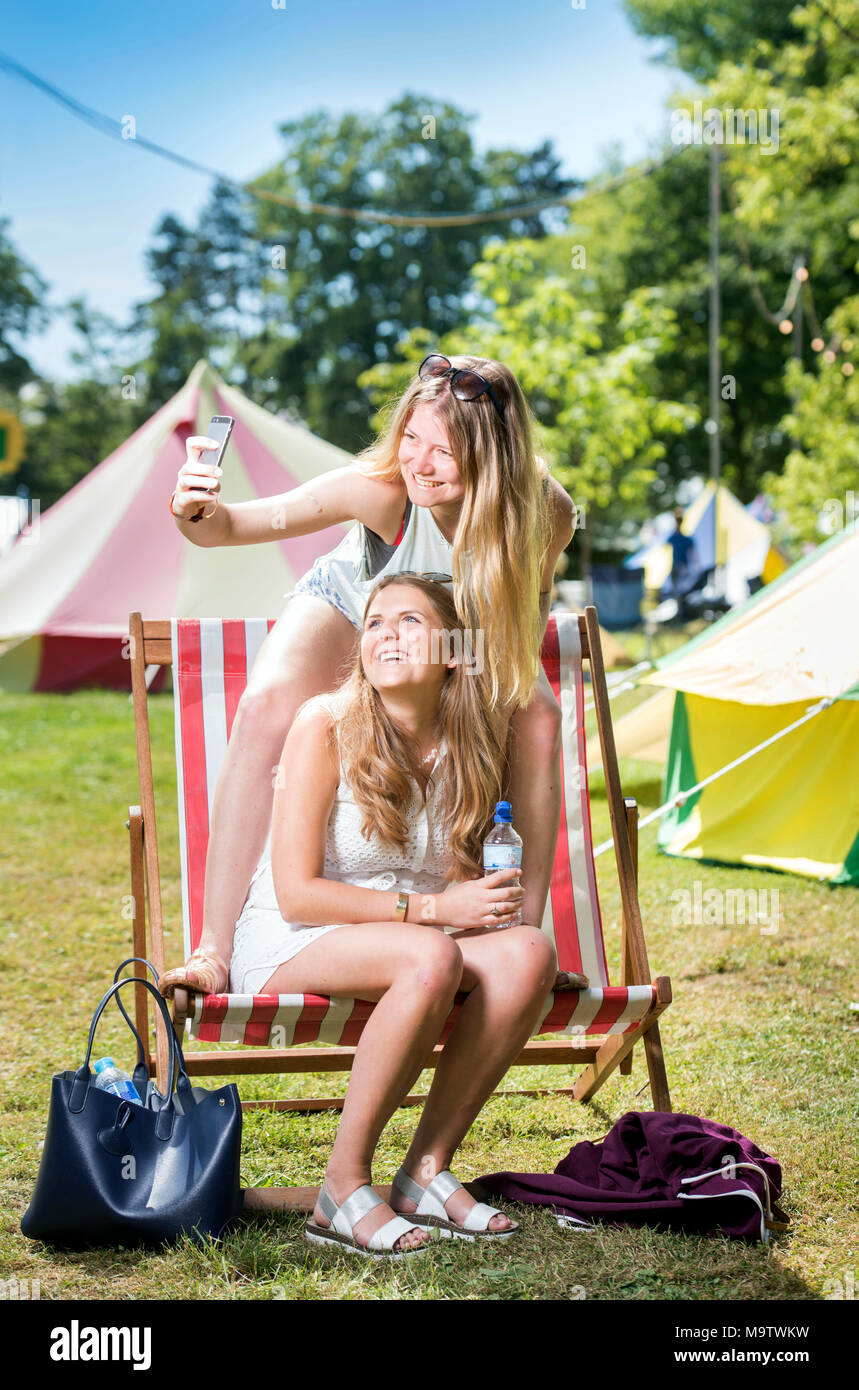 Girls take a selfie in a 'Glamping' area at the Cornbury Music Festival UK - Stock Image