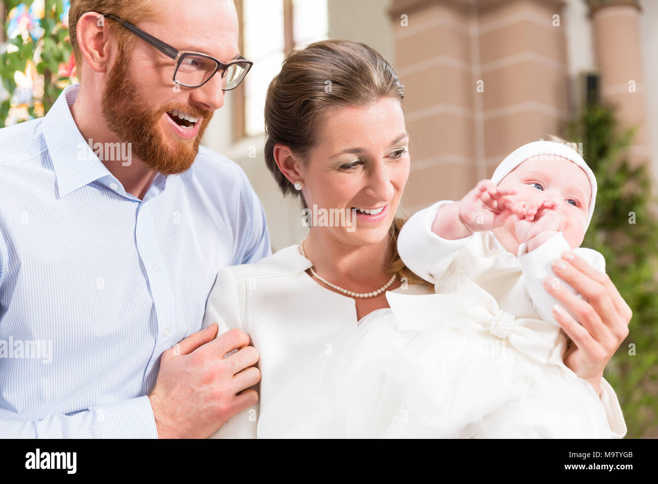 Parents with baby at christening in church - Stock Image
