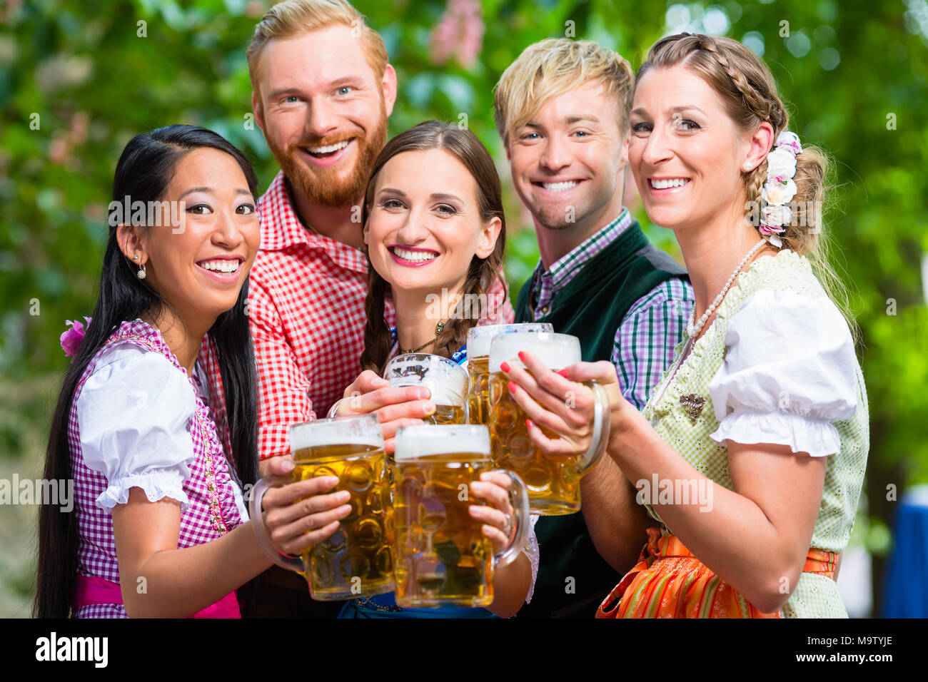 Friends having fun in beer garden while clinking glasses - Stock Image
