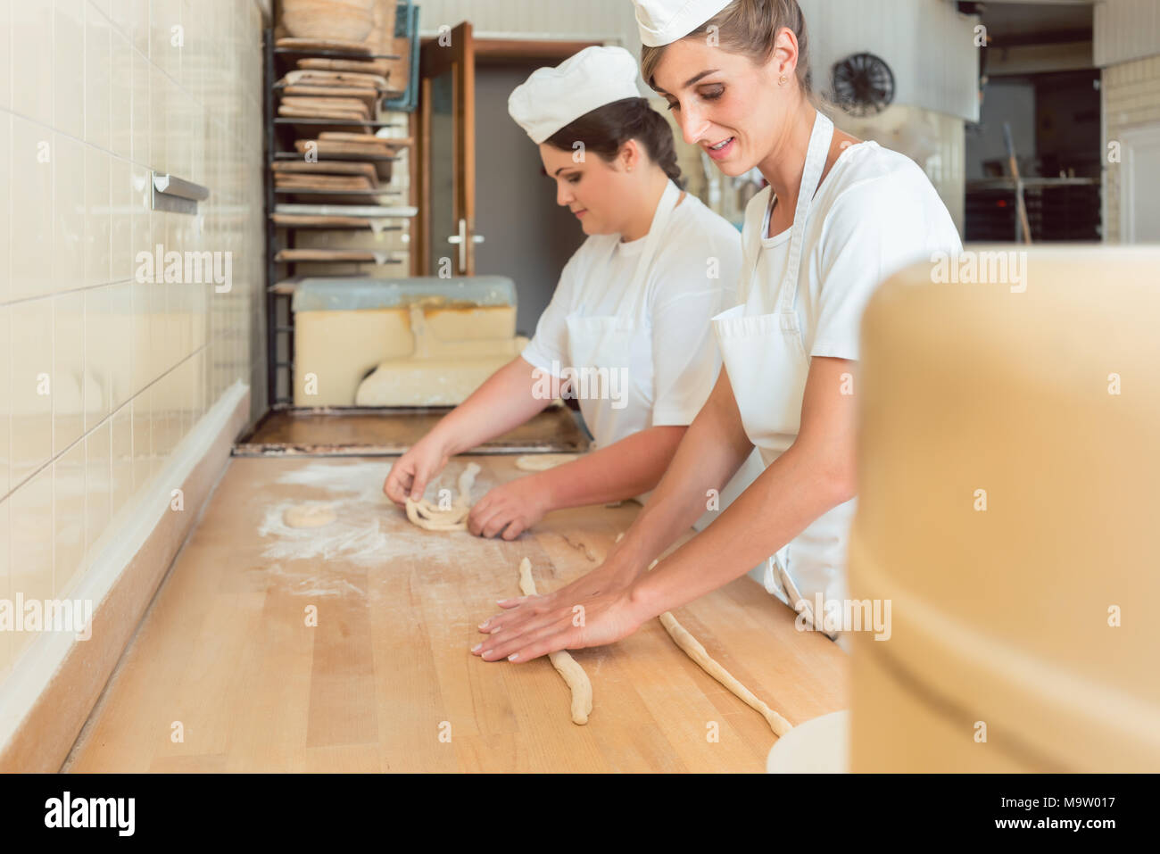 Women in bakery forming raw dough to pretzels - Stock Image